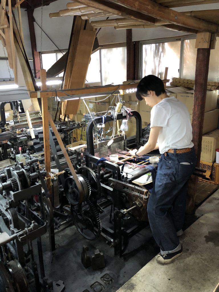 下川織物で作業中の西さん